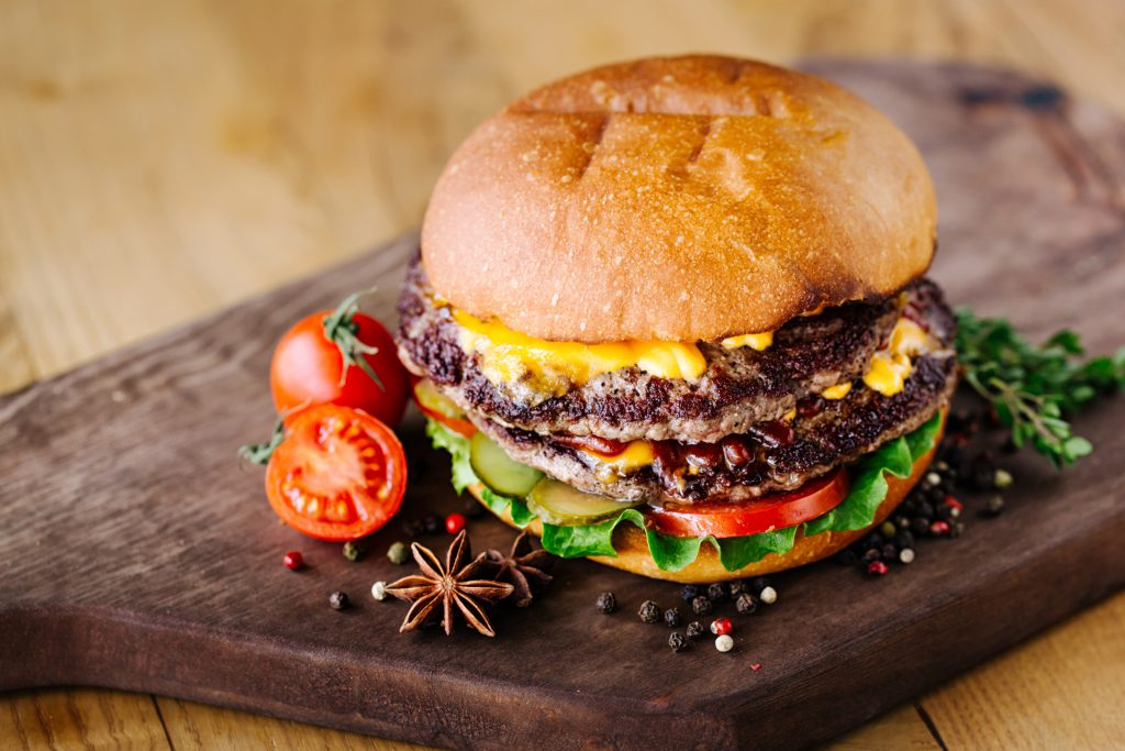 Juicy beef burgers on wooden background